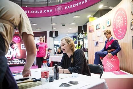 Taiteilija Mari Liimatainen työskenteli lauantaina Oulun suurlähetystö -tapahtumassa Kampin kauppakeskuksessa Helsingissä. Taustalla suurlähettilään roolissa näyttelijä Ernest Lawson.