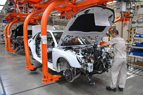 Työntekijä kokosi autoa China FAW Group Corporationin tehtaalla Changchunissa lokakuussa. Yhtiö valmistaa Kiinassa omien merkkiensä lisäksi myös Volkswagenia, Audia ja Toyotaa.