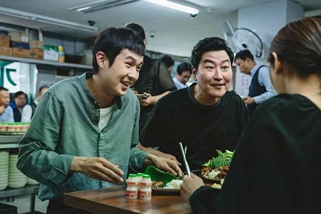 Työttömät Kimit ahmivat ravintolassa ruokaa ja lupausta paremmasta. Vasemmalla istuu perheen poika Ki-woo (Choi Woo-shik) ja oikealla isä Ki-taek (Song Kang-ho).