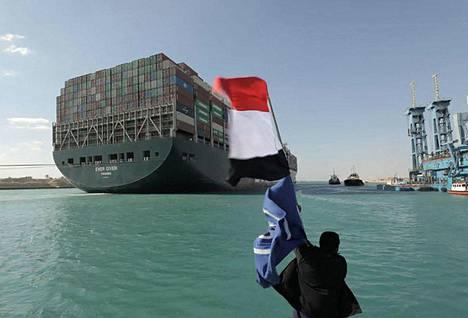 Mies heilutti Egyptin lippua Ever Given -alukselle Suezin kanaalissa maanantaina.
