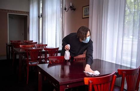 Hotelli Koidulaparkin johtaja Tiia Pärna puhdistaa ruokasalin pöytiä.