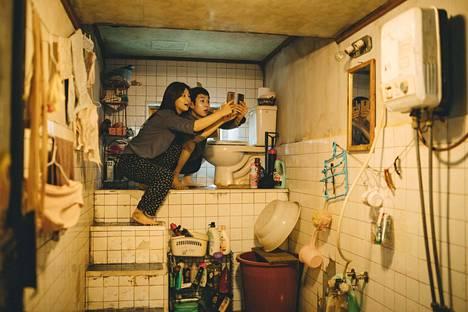 Kimin perheen aikuiset lapset kotinsa toiletissa etsimässä ilmaista wifiä. Tytärtä näyttelee Park So-dam ja poikaa Choi Woo-shik.