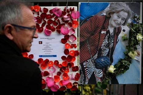Mies seisoi murhatun Mireille Knollin kuvan ja muistomarssista kertovan viestin edessä Knollin kotitalon edessä Pariisissa tiistaina.