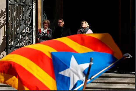 Katalonian entinen aluejohtaja Artur Mas (kesk.) ja entiset aluehallituksen ministerit Irene Rigau (vas.) sekä Joana Ortega poistuivat oikeustalosta Barcelonassa ensimmäisenä oikeudenkäyntipäivänään viime maanantaina. Etualalla heilui itsenäisyysmielisten tähtilippu.