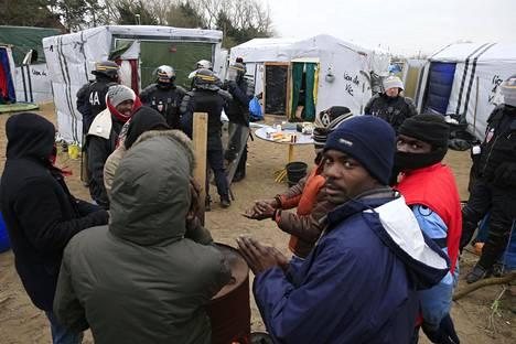 """Ranskalaiset poliisit tutkivat """"Jungle"""" nimistä turvapaikanhakijoiden leiriä Calaisissa Ranskassa tiistaina."""