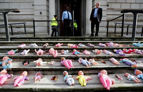 Kehitysapuleikkauksia vastustavat mielenosoittajat asettivat nukkeja Britannian valtiovarainministeriön portaille viime marraskuussa.