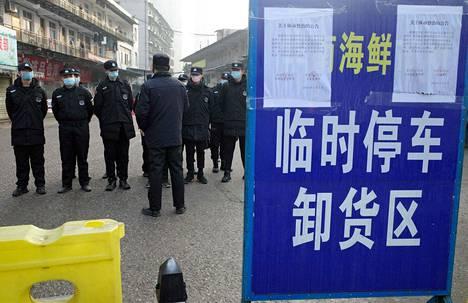 Vartijoita Wuhanissa Kiinassa suljetun torin edessä 12. tammikuuta. Mysteeriviruksen epäillään levinneen kyseiseltä kauppatorilta.