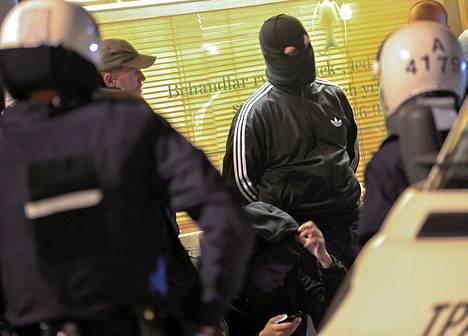 Tukholman Husbystä alkunsa saaneet mellakat ovat jatkuneet Ruotsissa jo lähes viikon. Kuva poliisit piriittävät lauantaina maskilla kasvonsa peittänyttä miestä.