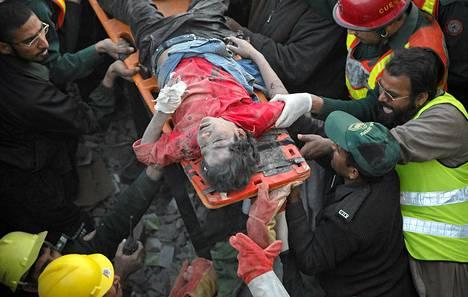 Pelastusmiehet nostavat loukkaantunutta poikaa romahtaneen tehtaan raunioista Lahoressa.