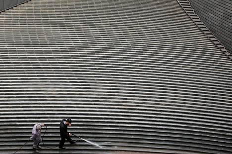 Siivoajat puhdistavat rappuja vasta-avatun toimistopilvenpiirtäjän edessä Pekingissä torstaina.