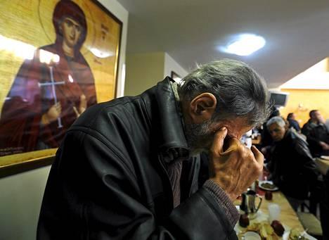 Mies rukoili ennen lounastaan kirkon järjestämässä, köyhille tarkoitetussa ruokapaikassa Ateenassa maaliskuun puolivälissä.