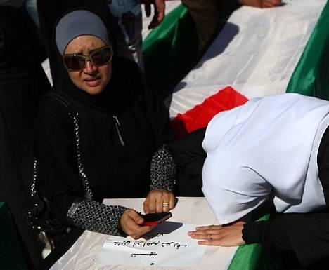 Palestiinalaisnaiset surivat lippuun käärityn palestiinalaistaistelijan arkun äärellä torstaina Ramallahissa Länsirannalla.