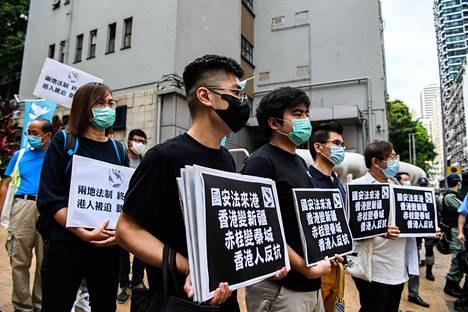 Demokratia-aktivistit kantoivat turvallisuuslakia vastustavia kylttejä perjantaina Hongkongissa.