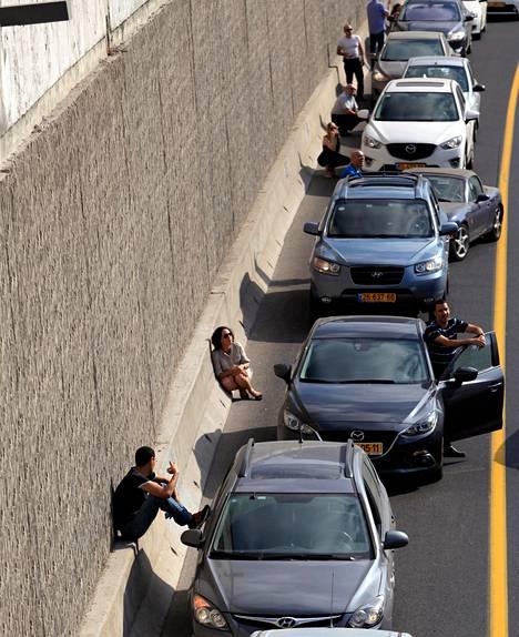 Autoiljat etsivät turvaa tien seinämän vierestä ilmahälytyksen varoittaessa uusista Tel Aviviin suunnatuista raketti-iskuista keskiviikkona.