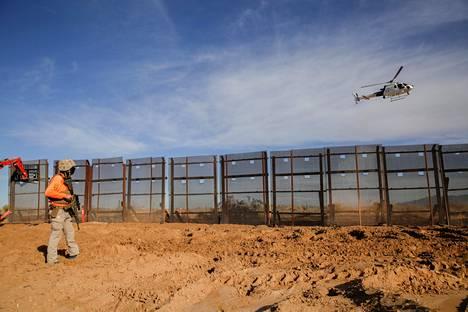 Yhdysvaltain tullin helikopteri lensi rajamuurin yläpuolella Meksikon Sunland Parkissa perjantaina.
