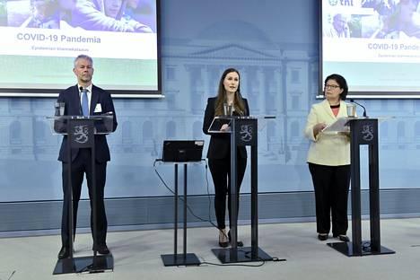 Ylilääkäri Taneli Puumalainen THL:stä (vas.), pääministeri Sanna Marin ja STM:n strategiajohtaja Liisa-Maria Voipio-Pulkki puhuivat hallituksen tiedotustilaisuudessa perjantaina.