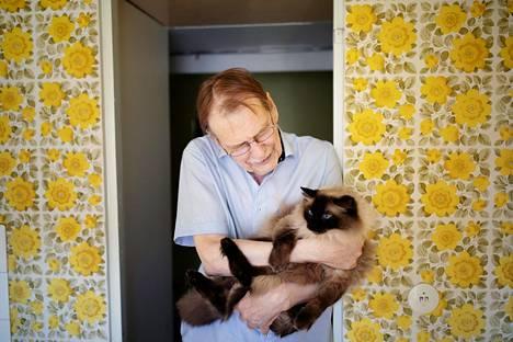 """""""Lähes jokaiseen kokoelmaani olen kirjoittanut sodanvastaisia runoja"""", sanoo Kari Aronpuro, jonka isä kuoli nuorena upseerina jatkosodan alussa 1941. Sylissä Umbra-kissa."""