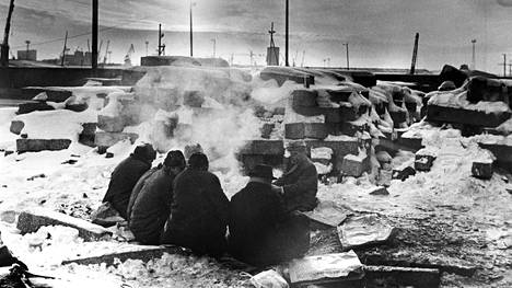 Asunnottomat miehet lämmittelivät nuotiolla sittemmin pois puretun Lönnrotinkadun sillan alla vuonna 1970. Taustalla näkyy kauempana Jätkäsaaren nostureita.