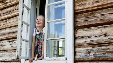 Aino Lappalainen, 12, kurkistaa ulos 1800-luvulla rakennetun savupirtin ikkunasta Huhkojärven tilalla.