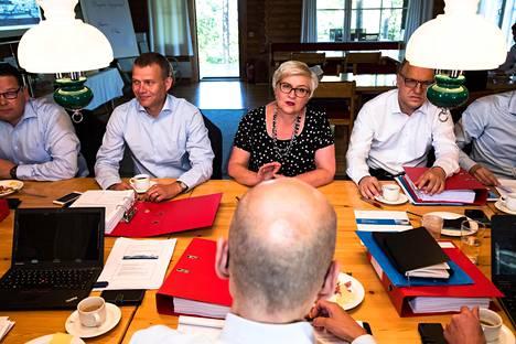Valtiosihteeri Martti Hetemäki (edessä) alusti hallituksen budjettineuvotteluita Espoon Moisniemessä tiistaina. Valtiovarainministeri Petteri Orpon (kok) vieressä Hetemäen kanssa keskustelee kunta- ja uudistusministeri Anu Vehviläinen (kesk).