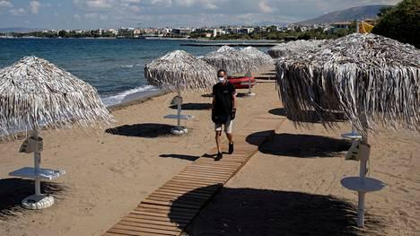 Hotellityöntekijä käveli rannalla Kreikan Ateenassa hotellien avattua ovensa 1. kesäkuuta.