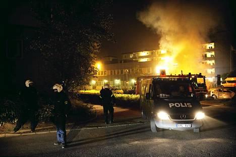 Poliisi ja pelastustyöntekijät seurasivat mellakkatilannetta Husbyn lähiössä Tukholmassa torstain vastaisena yönä.