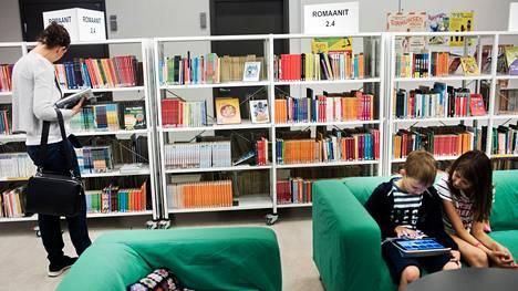 Suomeen suunnitellaan yhtä digikirjastoa. Sisarukset Emma ja Niko Meriheinä kirjastoin e-palveluiden äärellä vuonna 2016,