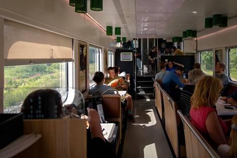 Matkustajia junan ravintolavaunussa.