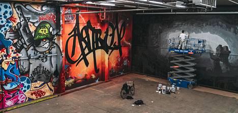 Monien Concreate-teosten mittakaava on suuri. Jesse Pasanen (oik.) työstää teostaan, vasemmalla seinällä graffitiryhmä Trama Teamin töitä.