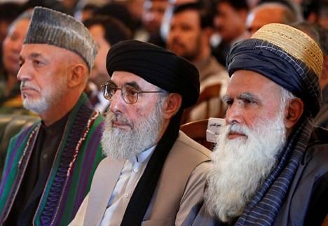 Entinen sotaherra Gulbuddin Hekmatyar (kesk.) istui kunniakseen järjestetyssä tervetulotilaisuudessa Afganistanin entisen presidentin Hamid Karzain (vas.) ja islamistijohtaja Abdul Rasul Sayyafin välissä presidentinpalatsissa Kabulissa torstaina.