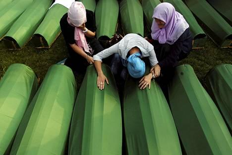 Bosnialaisnaiset surivat Srebrenican kansanmurhan uhrien arkkujen äärellä vuonna 2013. Arkuissa oli vastikään tunnistettujen uhrien jäänteitä.