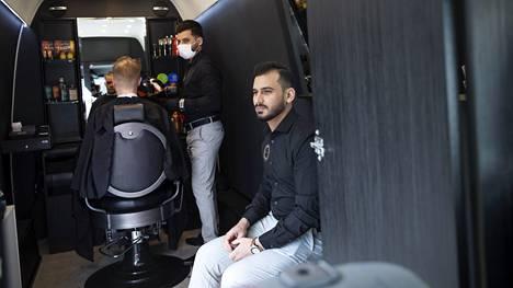 Parturi Mohammed Al-Khayyat leikkaa Matias Holmqvistin tukkaa parturipakettiautossa. Etualalla istuu toinen yrityksen perustajista, Ahmed Al-Khayyat. Holmqvist on toiminut Al-Khayyatien yritysneuvojana yrityskeskus Yritys Espoossa.