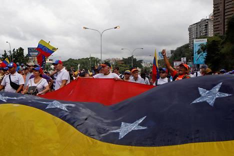 Opposition kannattajat kantoivat suurta lippua Caracasissa keskiviikkona.