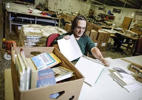 Roke Laitinen irrottaa kannet kirjoista, jolloin paperiset sisäsivut voidaan hyödyntää lämmöneristemateriaalina.