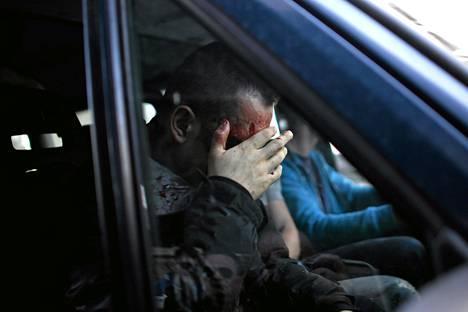 Pahoinpidelty poliisi piteli kasvojaan autossa hetki mielenosoittajien hyökkäyksen jälkeen.