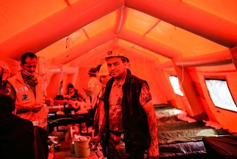 Pelastustöihin osallistunut kaivosmies seisoi terveydenhoitajien teltassa hengitettyään myrkyllisiä palokaasuja.