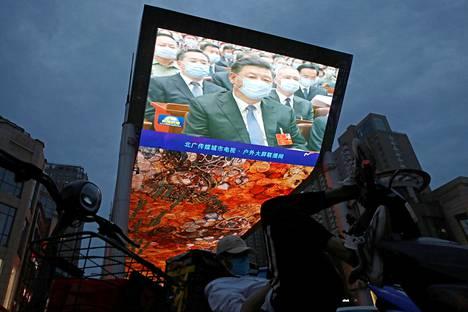 Kauppakeskuksen valotaululla Pekingissä näkyi kasvosuojassa kansankongressin avajaisiin osallistunut presidentti Xi Jinping.