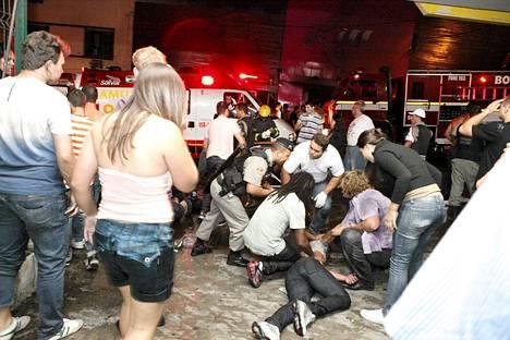 Poliiisi ja pelastushenkilökunta auttaa yökerhopalossa loukkaantunutta.