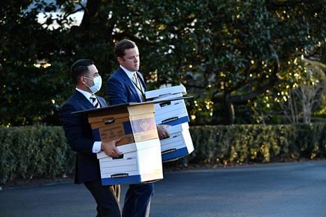 Presidentti Donald Trumpin avustajat kantoivat laatikoita Trumpin helikopteriin ennen presidenttiparin lähtöä Valkoisesta talosta keskiviikkona.