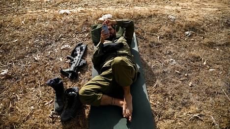 Israelin armeijan sotilas katseli puhelintaan levätessään Gazan rajalla marraskuussa 2017.