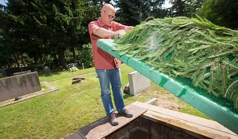 Malmin hautausmaan ylipuutarhuri Juha Ollila tarkastaa, etteivät vainajaa odottavan haudan seinämät ole romahtaneet kaivamisen jälkeen.