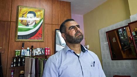 Bassam Hammad sanoo olevansa ylpeä marttyyrin isä. Seinällä on pojan kuva.