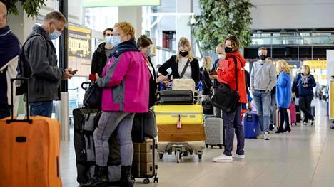 Hollantilaisia lomalle lähtijöitä huhtikuussa Schipholin lentokentällä Amsterdamissa. Osa lomakohteista on auennut turisteille, vaikka tarpeetonta matkustamista pyydetään välttämään.