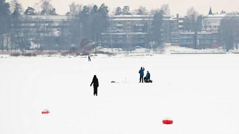 Ihmisiä heikoilla jäillä Hietarannan edustalla 18. tammikuuta. Taustalla Lauttasaari.
