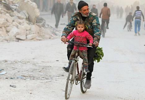 Mies ajoi polkupyörällä tyttärensä kanssa kapinallisalueella Itä-Aleppossa viime keskiviikkona.