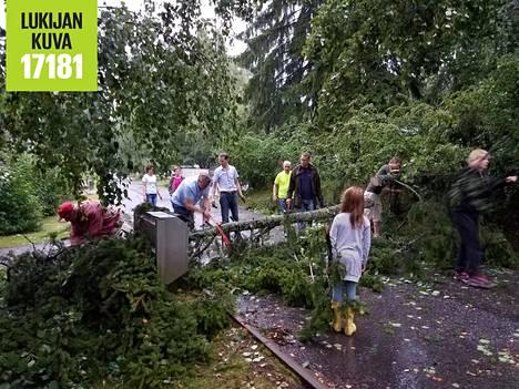 Tielle kaatunutta puuta poistetaan naapuruston voimin ennen palokunnan saapumista Pohjois-Tapiolassa Visakoivuntiellä.