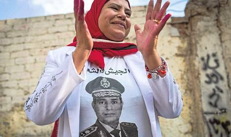 """Kairossa äänestäneellä naisella oli tiistaina yllään paita, jossa on kenraali Abdel Fattah al-Sisin kuva ja arabiankielinen teksti: """"Armeija ja kansa yhdessä terrorismia vastaan."""""""