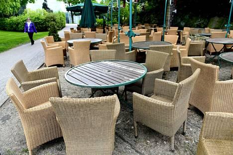 Ravintola Storyvillen terassilla Helsingissä tuolit ja aurinkovarjot olivat perjantaina valmiina ensi viikkoa varten.
