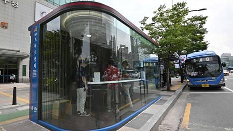 Matkustajia odottamassa bussia infrapunalampulla ja lämpökameralla varustetulla bussipysäkillä keskiviikkona Soulissa.