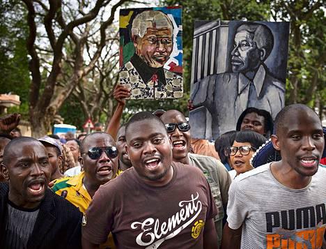 Ihmiset lauloivat ja tanssivat lauantaina edesmenneen ihmisoikeustaistelijan kodin edessä. Ivan Lukhelen (oik.) mielestä Nelson Mandela oli nykyajan Mooses.